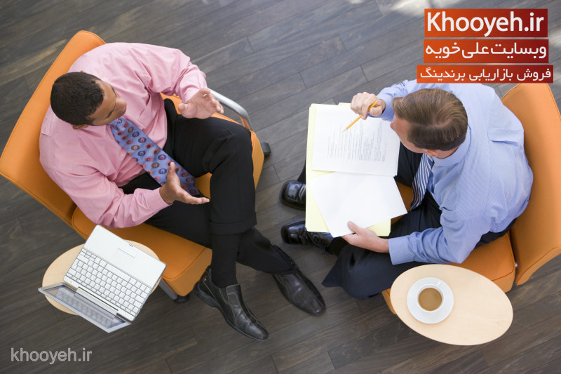 Two businessmen sitting indoors with coffee laptop and folder